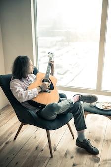 肘掛け椅子で休む。雪に覆われた街を見ながら、信頼できるアコースティック ギターを抱き締める感情的な黒髪の男