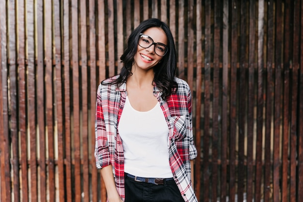 Resting latin woman in glasses standing on wooden wall. outdoor shot of spectacular girl enjoying spring photoshoot.