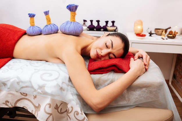 Resting on massage. peaceful long-haired client enjoying time alone in cabinet with herbal bags placed on her back