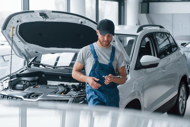 Отдыхая на рабочем месте. сотрудник в синей форме стоит в автомобильном салоне