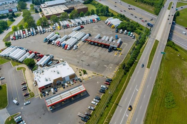 미국에서 주유소가 있는 고속도로에서 떨어진 주차장에 있는 다양한 유형의 트럭에 트럭 정류장을 놓으십시오.