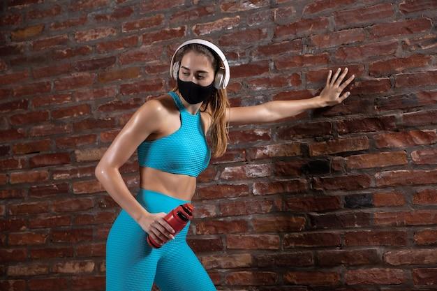 休憩。フェイスマスクを着用してレンガの壁でトレーニングするプロのアスリート。世界的大流行のコロナウイルスの検疫中のスポーツ。機器を使用して安全なジムで練習している若いカップル。