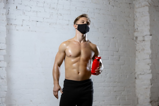 휴식. 얼굴 마스크를 쓰고 벽돌 벽에 훈련하는 프로 운동 선수. 전 세계적으로 유행하는 코로나 바이러스 격리 중 스포츠. 장비를 사용 하여 안전한 체육관에서 연습하는 젊은 부부.