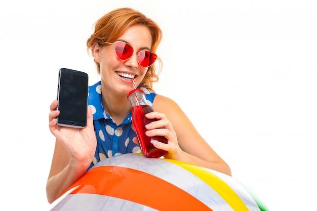 Отдыхая улыбающаяся девушка с очками с телефоном с макетом на белом фоне