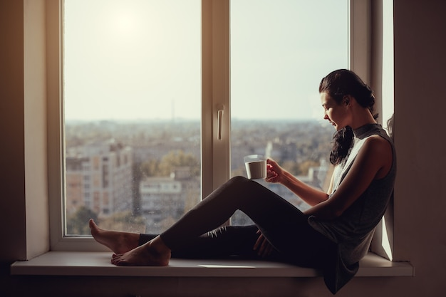 Resting and thinking woman. calm girl with cup of tea or coffee sitting on the window-sill at