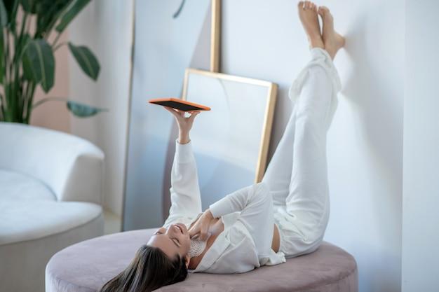 휴식. 그녀의 다리를 위로 누워 태블릿을 들고 백인 젊은 여자