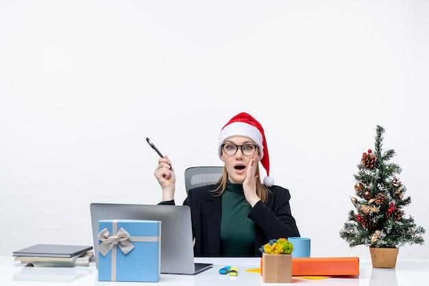 Беспокойная блондинка в шляпе санта-клауса сидит за столом с елкой и подарком на ней на белом фоне