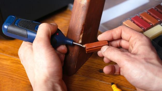 Реставрация ремонт деревянной поверхности на мебели, герметизация царапин и сколов набор инструментов крупным планом.