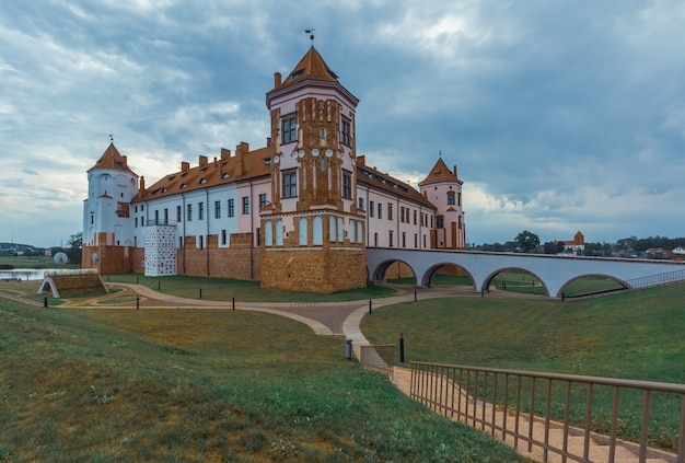 Restored castle in belarus city of mir. summer landscape with architecture
