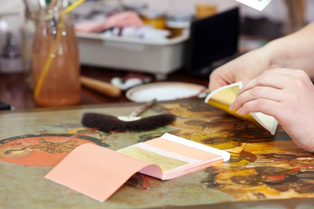 Restorer gilding on the old icon