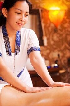 Restoring life balance. confident thai massage therapist massaging female back and smiling