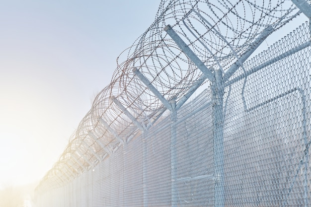 Restricted area fence against blue sky closeup barbed wire classified state zone migration problem concept