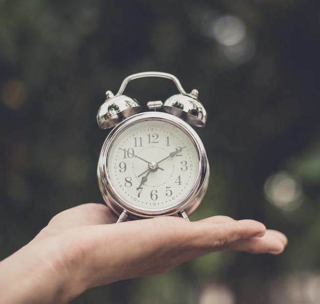 手にレトロな目覚まし時計。時間が実行されています。