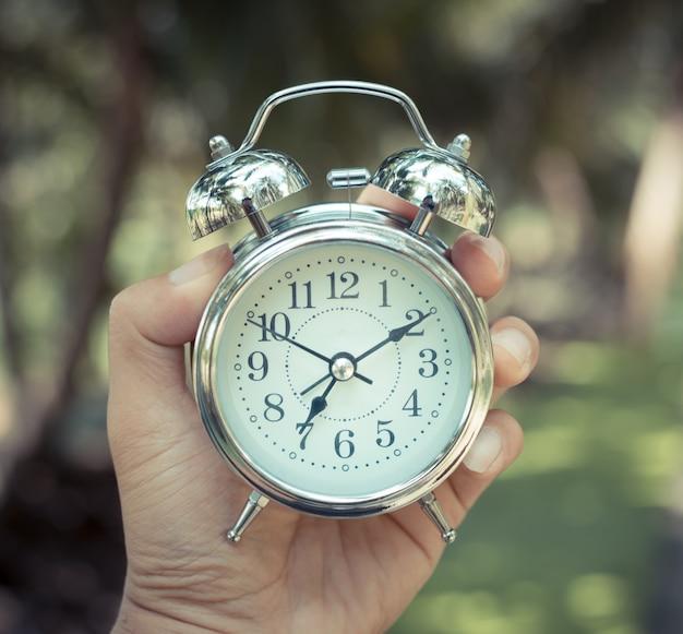 Restro классический будильник в руке. время бежит.