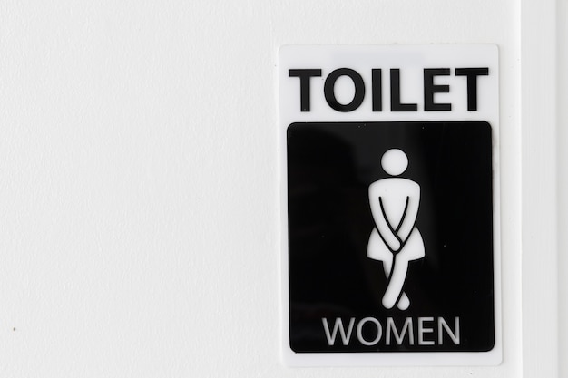 Restroom sign with copy space on white wall