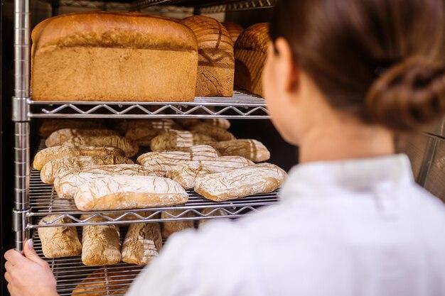労働の結果。焼きたての食欲をそそる小麦パンのラックを見てカメラに背を向けて立っている女性、顔が見えない Premium写真