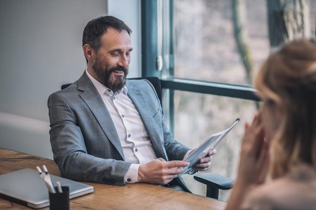 結果、レポート。ドキュメントを読んでビジネススーツの重要な大人の上司と結果を待っている女性アシスタントの笑顔