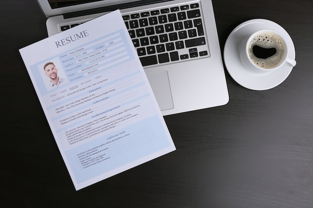 Resume and laptop on wooden table