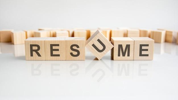 履歴書-灰色の背景に文字が書かれた木製のブロックの単語。テーブルの鏡面にキャプションが反映されています。セレクティブフォーカス。