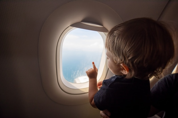 Resumption of flights, opening of borders concept. a small child looks at the ocean from the window of a flying plane. first flight. vacation happiness. soft focus