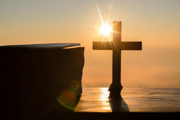예수 그리스도 개념의 부활 : 언덕 일출 배경에 실루엣 십자가