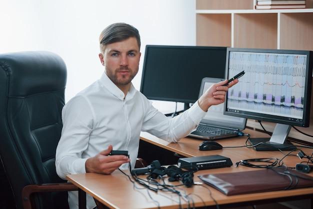 Resutsは明日になります。ポリグラフ検査官は彼の嘘発見器の機器を使用してオフィスで働いています