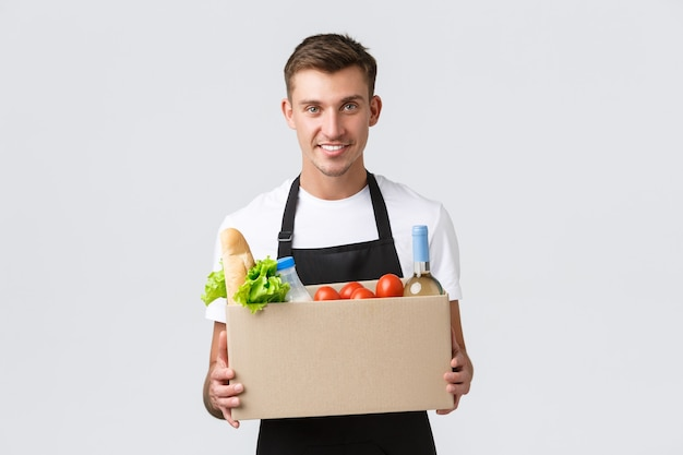 Retail grocery shopping and delivery concept handsome courier in black apron handing over box with g...