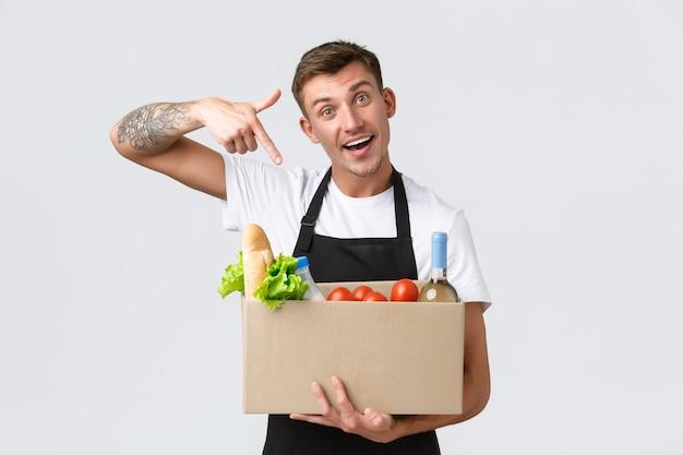 Concetto di acquisto e consegna di generi alimentari al dettaglio corriere bello in grembiule nero che consegna scatola con g...