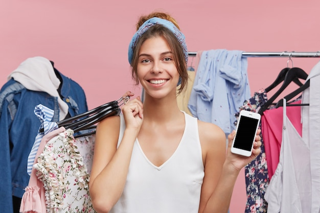 Retail, sale, consumerism and modern technology concept. portrait of charming young female standing at rack with fashionable clothes, enjoying shopping at mall, paying with online app on cell phone