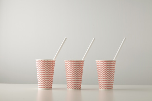 Retail set of three paper cups decorated with red line pattern and with white drinking straw inside isolated on white table