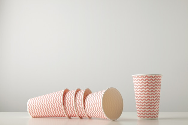 Retail set of three paper cups decorated with red lines pattern felt down and one standing near isolated on white table