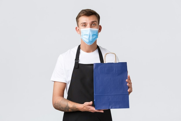 小売店、covid-19での買い物、社会的距離の概念。フレンドリーで丁寧なセールスマン、医療用マスクと黒いエプロンのバリスタ、エコバッグに購入したアイテムを入れ、白い背景に立って
