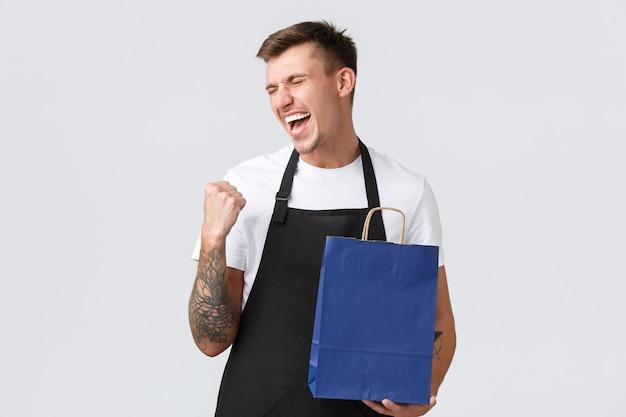 Concetto di negozio al dettaglio, shopping e dipendenti. allegro venditore felice che si gode finalmente di lavorare dopo il covid-19, pompa a pugno e cantando dalla felicità, tenendo in mano una borsa ecologica, sfondo bianco