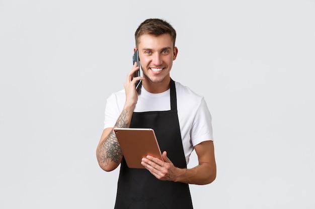 소매점, 중소기업, 카페, 레스토랑 테이크아웃 컨셉입니다. 잘생긴 웃는 세일즈맨, 바리스타가 전화 통화를 하고, 행복하게 웃고, 배달 주문을 받고, 디지털 태블릿을 들고