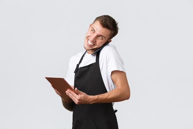 Retail stores, small business, cafe and restaurants takeaway concept. handsome young shop manager, employee receiving order over phone, talking with customer and writing down info in digital tablet