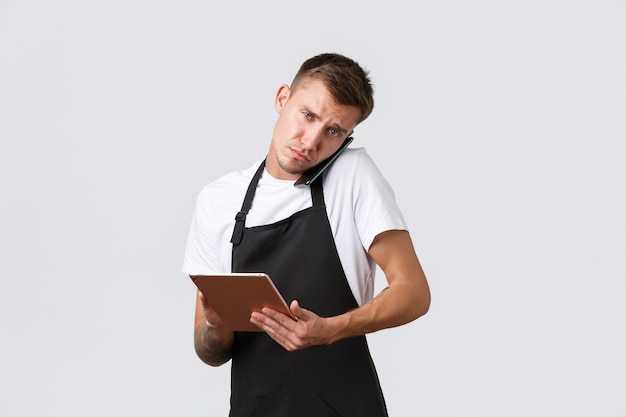 Retail stores, small business, cafe and restaurants takeaway concept. serious busy salesman talking with delivery company or client, holding smartphone on shoulder and using digital tablet