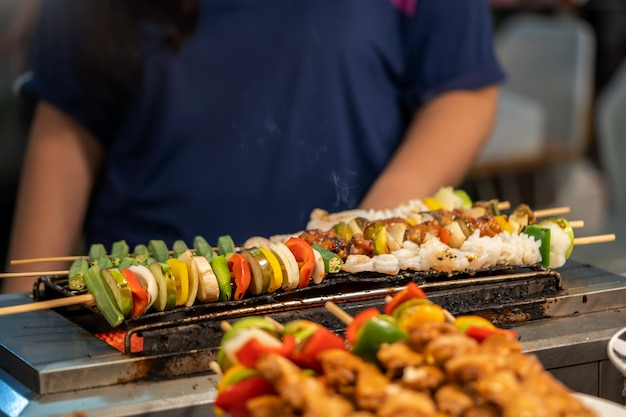 Retailer is grilling bbq skewer on hot griller for customer Premium Photo