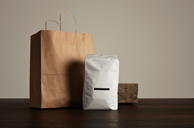 Пакет товаров для розничной торговли: большой герметичный пакет белого цвета с пустой этикеткой рядом с бумажным пакетом и деревенским деревянным кирпичом на красном столе.