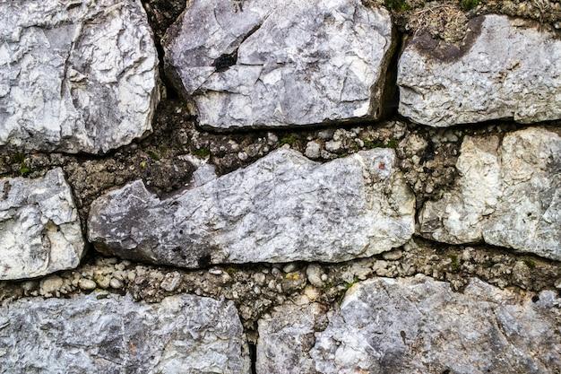 Удерживающая каменная стена рядом с дорогой. стальная сетка из габионной стены.