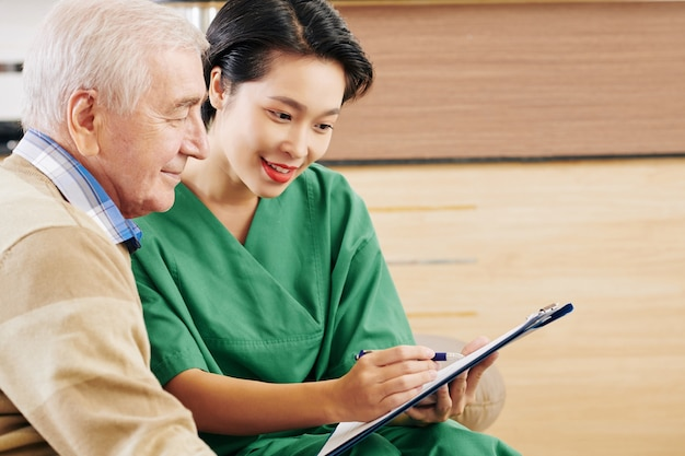 Retiment home volunteer talking to senior man