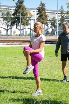 公園の芝生で朝の運動をしているスポーツ服を着て引退したアクティブな成熟した人々。タイツとスニーカーで脚を伸ばしている女性。退職またはアクティブなライフスタイルの概念