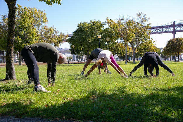 Retired active mature people wearing sports clothes, doing morning exercise on park grass, stretching back and legs muscles. retirement or active lifestyle concept