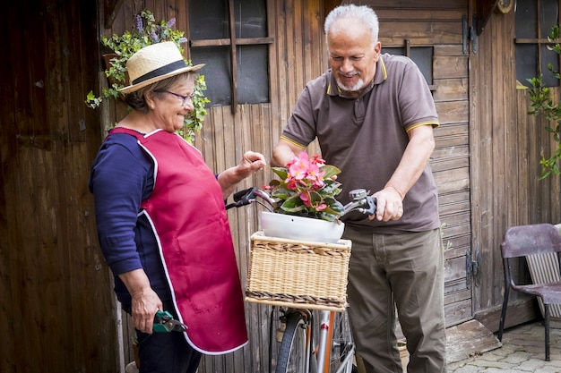Retired adult caucasian couple stay in the garden at his own home to work on the plants and vegetables. old style bike with them