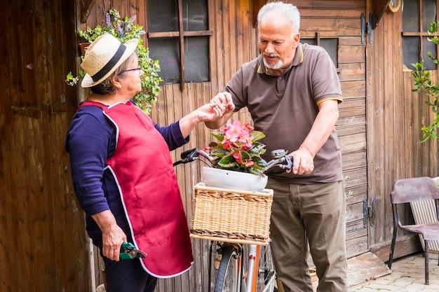 Пенсионерская пара взрослых кавказцев остается в саду в своем собственном доме, чтобы работать над растениями и овощами. велосипед старого стиля с ними