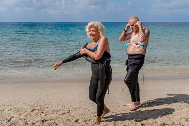 은퇴한 부부는 수영을 하기 위해 해변에서 잠수복을 입고 있습니다.
