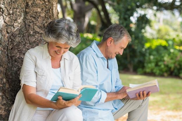 은퇴 한 부부 함께 책을 읽고 나무 줄기에 앉아