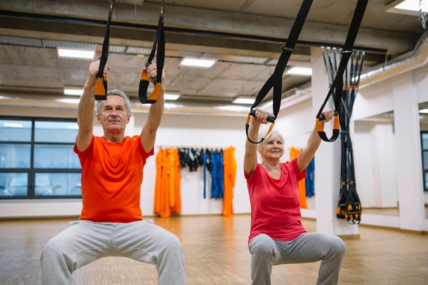 Retired couple training with rope in gym