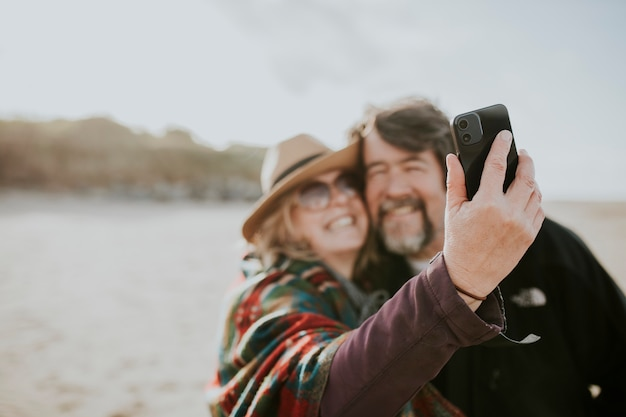 Retired couple on a trip take a selfie by the beach