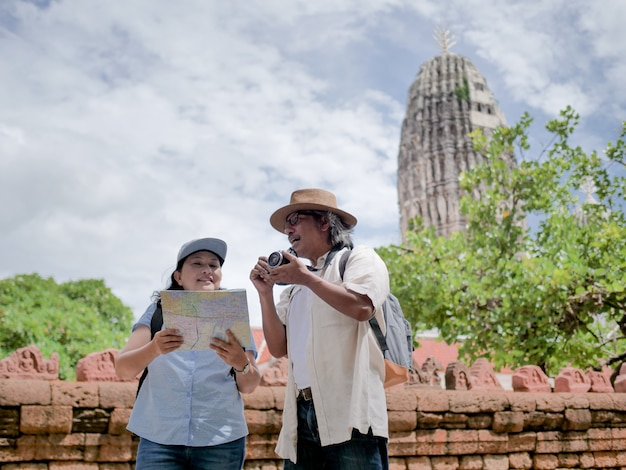 Retired couple walking around the town with a map. summer traveler concept.
