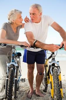 ビーチで自転車に乗って退職した夫婦
